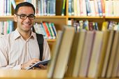 Portrait of a smiling mature student using tablet PC against bookshelf in the library