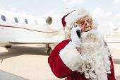 picture of nicholas  - Surprised Santa Claus using mobile phone against private jet at airport terminal - JPG