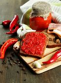 Composition with salsa sauce on bread,, red hot chili peppers  and garlic, on napkin,  on wooden bac