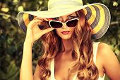 stock photo of charming  - Beautiful young woman in elegant hat and sunglasses posing outdoor - JPG