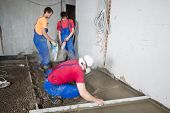 Three workers poured concrete floor in construction room