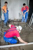 picture of breather  - Three workers in construction room prepare the mixture and pouringl the floor - JPG