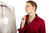 stock photo of heatwave  - businesswoman is cooling herself with an electric fan - JPG