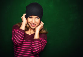 stock photo of cheeky  - Young beautiful happy girl cheeky teenager in a black hat and a pink dress on a green background - JPG