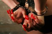 image of prostitution  - Sexy lady with handcuffs by the wall - JPG