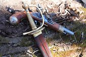 stock photo of saber  - Closeup of ancient saber near pistol on gray old wooden log - JPG
