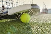 stock photo of paddling  - Paddle Tennis racket ball and net with flare light - JPG