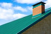 picture of downspouts  - chimney on the roof of the house against the blue sky - JPG