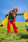 Man In Ski Suits Giving Piggyback Ride To Girlfriend With Snowboard  On The Grass Under The Sky