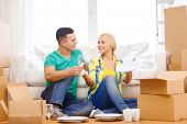 moving, home and couple concept - smiling couple unpaking boxes with kitchenware in new home