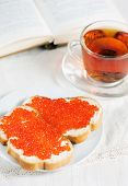 Red Caviar On A Slice Of Bread, Tea And Open Book