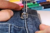 stock photo of sewing  - Sewing machine and item of clothing trousers jeans material - JPG