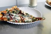 stock photo of pizza parlor  - A slice of pizza on a paper plate in a store front Pizzeria - JPG