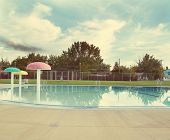 a local public pool without any people in it as sunset done with a retro vintage instagram like fil
