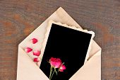Old envelope with blank photo paper and beautiful pink dried roses on wooden background