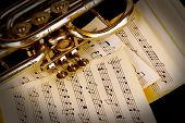 stock photo of orchestra  - Musical notes and trumpet on wooden table - JPG