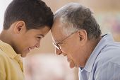 stock photo of pre-adolescents  - Older man touching foreheads with his grandson - JPG