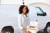 image of cake stand  - Female Baker Delivering Cakes Standing In Front Of Van - JPG