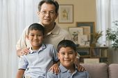 foto of pre-adolescents  - Father and sons smiling for the camera - JPG
