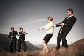 pic of tug-of-war  - Competitive business people struggling to win tug - JPG