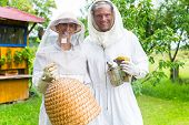 picture of smoker  - Beekeeper team working outdoor with smoker and beehive   - JPG