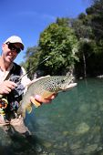 picture of fly rod  - Fly fisherman holding fario trout recently caught - JPG