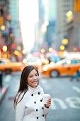 stock photo of cabs  - Young casual urban professional business woman in New York City Manhattan drinking coffee walking in street wearing coat downtown with yellow taxi cabs in background - JPG