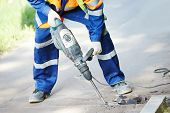 picture of construction machine  - Builder worker with pneumatic hammer drill equipment breaking asphalt at road construction site - JPG