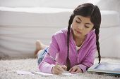foto of pre-adolescent girl  - Young Hispanic girl doing homework on the floor - JPG