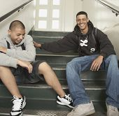stock photo of pacific islander ethnicity  - Two young men laughing on stairs at school - JPG