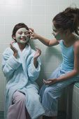foto of pre-adolescent girl  - Two young girls applying facial masks in bathroom - JPG