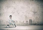 foto of tricycle  - Little joyful cute boy riding tricycle on road - JPG
