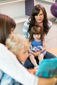 picture of lap  - Cute little girl sitting on teacher - JPG