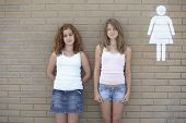 image of pre-adolescent girl  - Two teenage girls leaning against wall next to restroom sign - JPG
