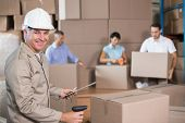 stock photo of warehouse  - Warehouse workers preparing a shipment in a large warehouse - JPG