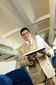picture of flight attendant  - Low angle view of Hispanic male flight attendant carrying wine on a tray - JPG