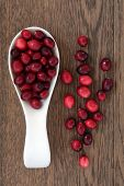 image of spoon  - Cranberry fruit in a wooden spoon over oak wood background - JPG