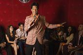 picture of karaoke  - Mixed Race man singing karaoke at nightclub - JPG