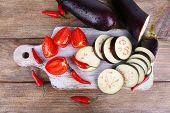 foto of brinjal  - Chopped aubergines with tomatoes and chilly pepper on cutting board on wooden background - JPG