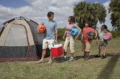 picture of sleeping bag  - Hispanic family holding sleeping bags next to tent - JPG