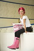 image of laundromat  - Tattooed Hispanic woman in laundromat - JPG