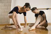 image of ballet shoes  - Hispanic female ballet dancers fastening shoes - JPG