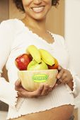 image of fruit bowl  - Pregnant Mixed Race woman holding bowl of fruit - JPG