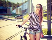 foto of toned  - Trendy Hipster Girl with Bike on Urban Background - JPG