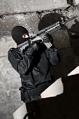 foto of extremist  - Armed terrorist moving up the staircase with a gun in his hands - JPG