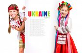picture of national costume  - two little girsl in the Ukrainian national costume stand behind white board with space for text - JPG