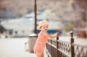 stock photo of jumpsuits  - Cute little girl in a pink Panama with white polka dots and pink summer jumpsuit with white polka dots - JPG