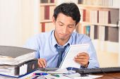 stock photo of overwhelming  - young stressed overwhelmed business man with piles of folders on his desk  - JPG
