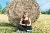 picture of haystack  - Young girl sitting with tablet close to haystack in meadow - JPG