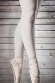 picture of ballerina  - Ballerina standing en pointe against wooden planks - JPG
